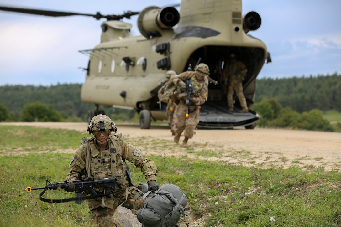 Troops in camouflage uniforms scramble out of helicopter as one soldier crouches on the ground with a weapon.