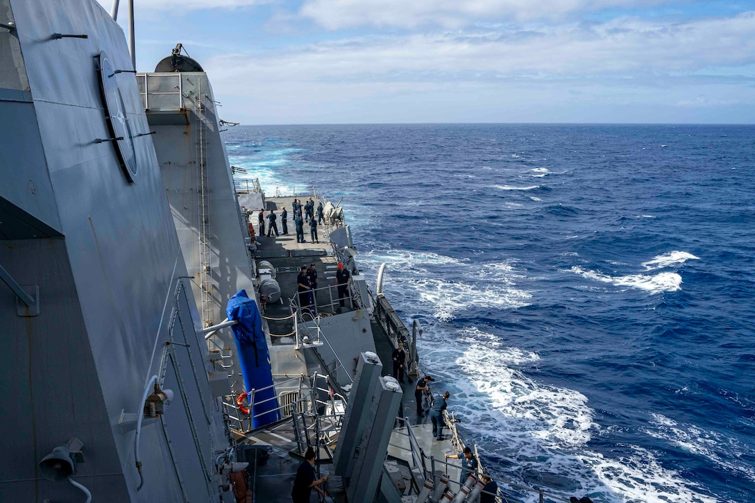 Sailors stand on the deck of a ship in the middle of the ocean.