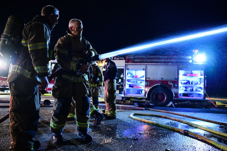 "Chief Master Sgt. Christopher Walker, 75th Air Base Wing command chief, operates a hose during a ""live fire"" with base firefighters Oct. 1, 2019, at Hill Air Force Base, Utah. The fire was part of a Hill AFB Fire and Emergency Services training demonstration to showcase the capability of a new, 100-foot ladder truck the department acquired this summer. (U.S. Air Force photo by R. Nial Bradshaw) (U.S. Air Force photo by R. Nial Bradshaw)"