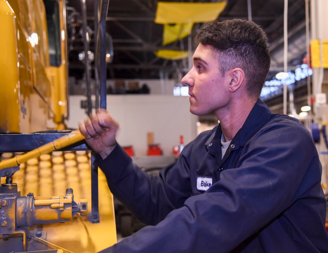 U.S. Air Force Airman Nathaniel Baker, 92nd Logistics Readiness Squadron vehicle maintainer, pumps the handle on an Oshkosh broom sweeper vehicle that opens the rear engine cover