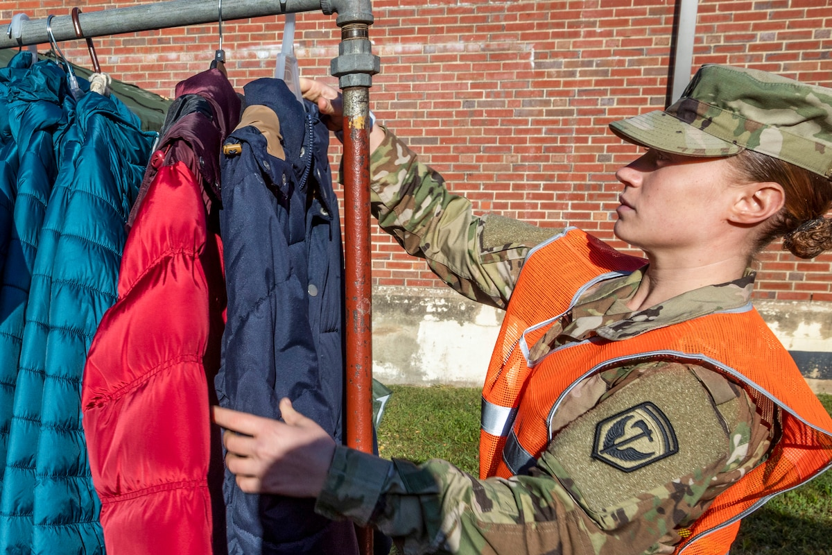 A soldier arranges winter coats on a clothing rack outside a brick building.
