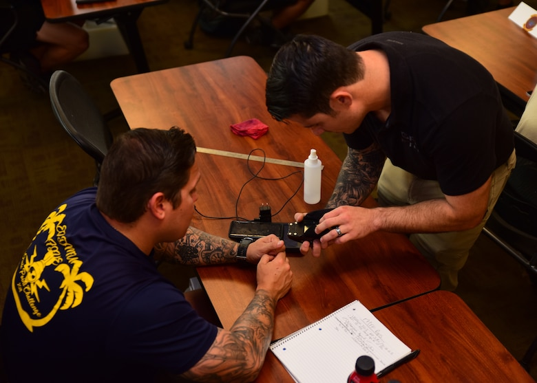 U.S. Air Force Staff Sgt. Travis Holmes, 68th Rescue Squadron air operations instructor, shows a student how to use a piece of equipment during the Guardian Angel Military Freefall Jumpmaster Course at Davis-Monthan Air Force Base, Arizona, Sept. 27, 2019. This course is accredited by the United States Department of Defense Special Operations Command and is one of only four in the entire DoD. (U.S. Air Force photo by Airman 1st Class Jacob T. Stephens)