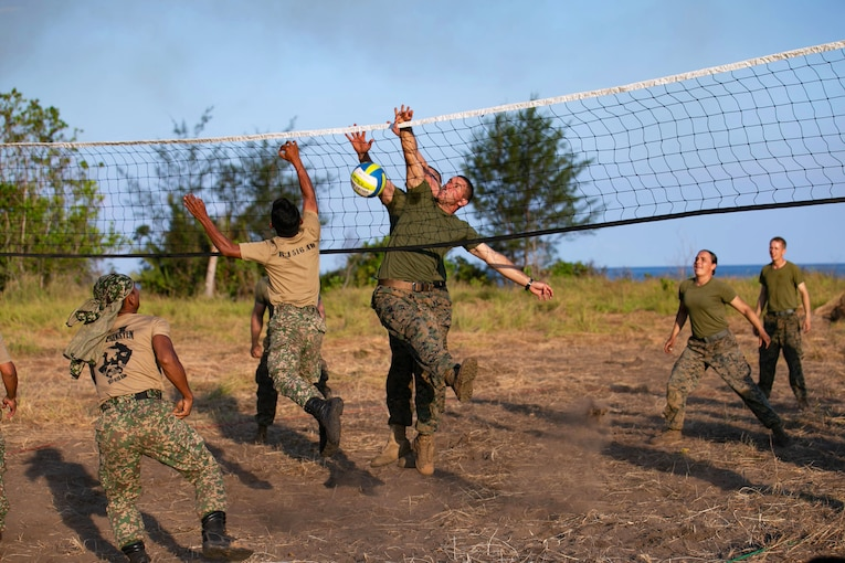 A group of U.S. and Malaysian service members play beach volleyball.
