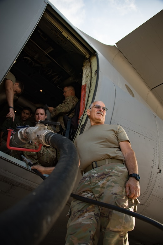 California Air National Guard Master Sgt. Bart Panighetti  connects a hose that loads water into the Modular Airborne Fire Fighting System (MAFFS II) inside of a retrofitted C-130J at the Channel Islands Air National Guard Station, Port Hueneme, CA. Aug. 24, 2019. (U.S. Air National Guard photo by Tech. Sgt. Nieko Carzis.)