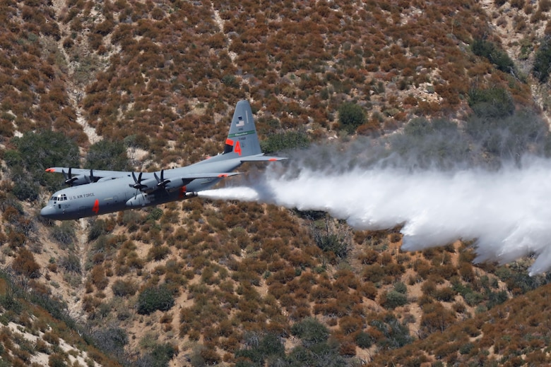 A C-130J aircraft retrofitted with the Modular Airborne Fire Fighting System (MAFFS)  performs a water drop during a training exercise at the Los Padres National Forest north of Santa Clarita, CA. Aug. 24, 2019. (U.S. Air National Guard photo by Senior Airman Todd Senff.)