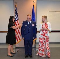 """Janie Purvis """"pins"""" new chief master sergeant stripes onto her husband Steven N. Purvis, 74th Aerial Port Squadron superintendent of programs, while his daughter Haleigh watches during a promotion ceremony Oct. 5, 2019 at Joint Base San Antonio-Lackland, Texas."""