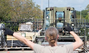 """Senior Master Sgt. Mary Adamson, 41st Aerial Port Squadron superintendent of the air terminal operations center, directs Master Sgt. Kenneth Holmes, 41st APS non-commissioned officer in charge of load planning, during the forklift obstacle course portion of the 2019 Port Dawg Challenge at Keesler Air Force Base, Miss., Oct. 5. Adamson and Holmes, part of team """"Old Skool"""", posted the fastest time, 3 minutes and 32 seconds, during this event. (U.S. Air Force photo by Senior Airman Kristen Pittman)"""