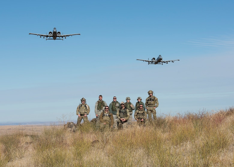 A pair of A-10 Thunderbolt IIs assigned to the 190th Fighter Squadron flies over a group of Airmen from the 124th Fighter Wing at the Saylor Creek Bombing Range, Idaho, Oct. 5, 2019