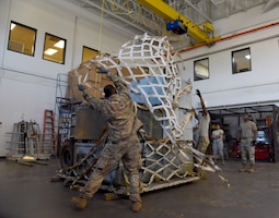 Members of the 41st Aerial Port Squadron drape cargo netting over a pallet of cargo as their teammates look on during the cargo pallet buildup portion of the 2019 Port Dawg Challenge at Keesler Air Force Base, Miss., Oct. 5. Cargo pallet buildup was one of five events of the competition and tested Airmens's speed and effectiveness when securing cargo. (U.S. Air Force photo by Senior Airman Kristen Pittman)