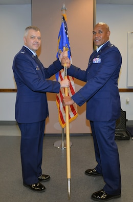 Col. Wayne M. Williams, 433rd Mission Support Group commander, hands the 26th Aerial Port Squadron guidon to Lt. Col. Eric L. Chancellor signaling his squadron command assumption.