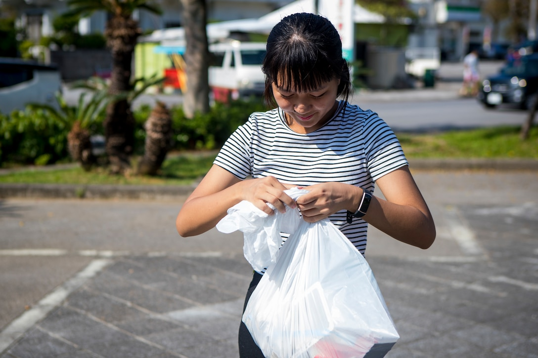 A member of the local community gathers trash during the monthly Friendship Cleanup in Uruma City, Okinawa, Japan on Oct. 5, 2019. The Camp Courtney Single Marine Program coordinates the cleanup every month to provide service members the opportunity to volunteer for community service and build friendly relationships with the local community.