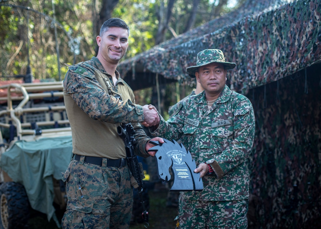 U.S. Marine Corps Maj. Kyle Padilla, the company commander with Lima Company, Battalion Landing Team, 3/5, 11th Marine Expeditionary Unit, gives a plaque to a member of the Malaysian Armed Forces. U.S. Marines and Sailors joined Malaysian Armed Forces for exercise Tiger Strike 2019 where both forces participated in jungle survival, amphibious assault, aerial raids, and combat service support training and cultural exchanges.