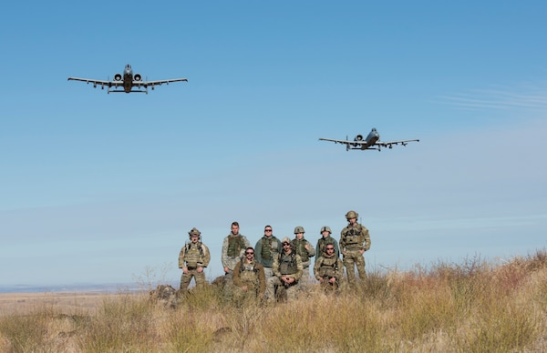 A pair of A-10 Thunderbolt IIs assigned to the 190th Fighter Squadron flies over a group of Airmen from the 124th Fighter Wing at the Saylor Creek Bombing Range, Idaho, Oct. 5, 2019. The range provides a designated area for pilots, Tactical Air Control Party Airmen and other mission-essential groups to run training missions.