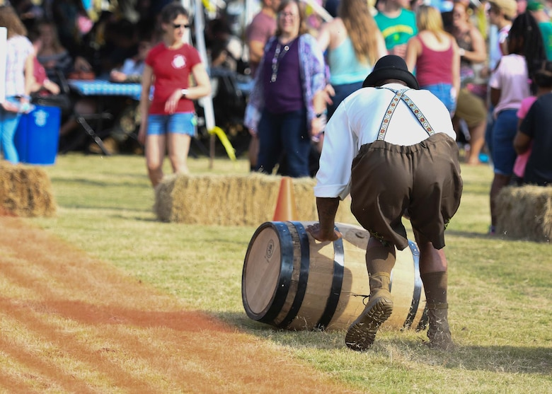 A guy rolls a barrel across the grass during Oktoberfest