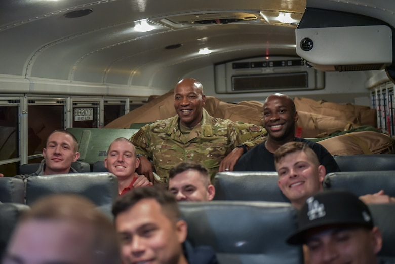 Chief Wright poses for a photo with a bus ful of Airmen