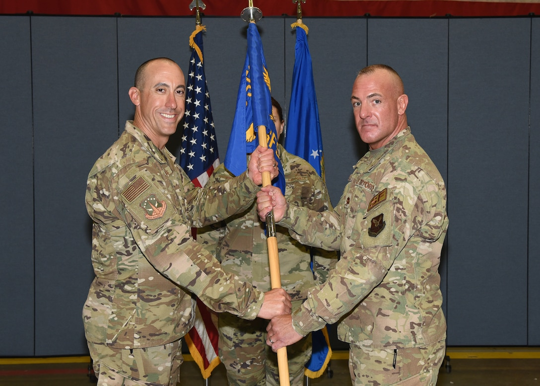 Colonel Damian Schlussel, 90th Security Forces commander, passes the guidon to Maj. George Hern, 90th Security Forces Squadron commander, during the 90th SFS assumption of command ceremony October 3, 2019 in the Peacekeeper Security Forces high bay on F.E. Warren Air Force Base, Wyo. The passing of the guidon symbolizes the authority and responsibility Hern now has as the commander of 90th SFS.  (U.S. Air Force photo by Glenn S. Robertson)