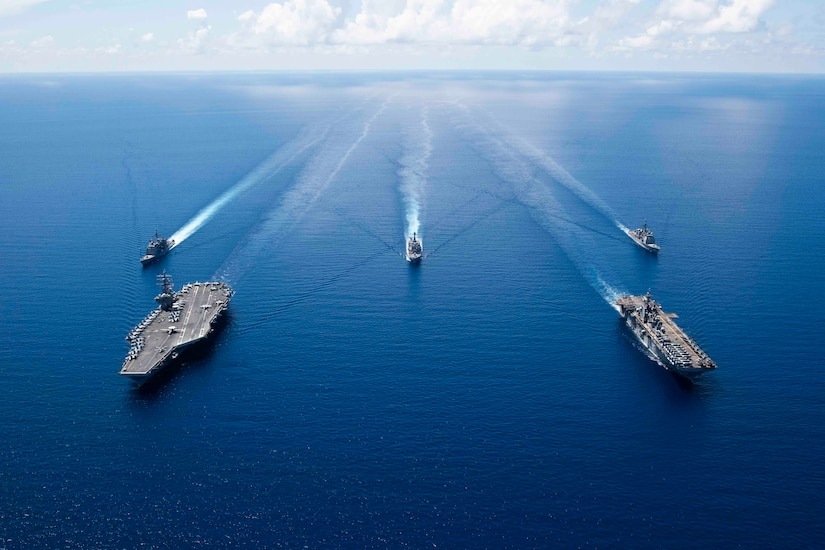 A group of ships sail in formation.