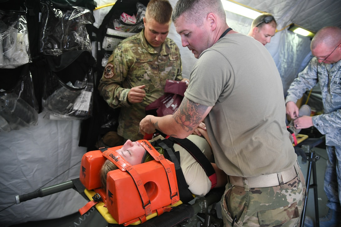 Airmen from 729th Air Control Squadron work together to aid a simulated spinal injured Airman Sept. 23, 2019, during Self-Aid Buddy Care training at a base camp at Wendover Field, Utah. The Airmen were participating in the squadron's annual Raging Bull exercise, where they set up a remote radar site to extend the unit's capability to control aircraft. (U.S. Air Force photo by Cynthia Griggs)
