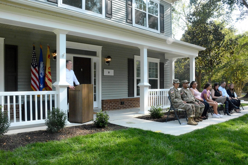 A man stands at a podium on a house porch.