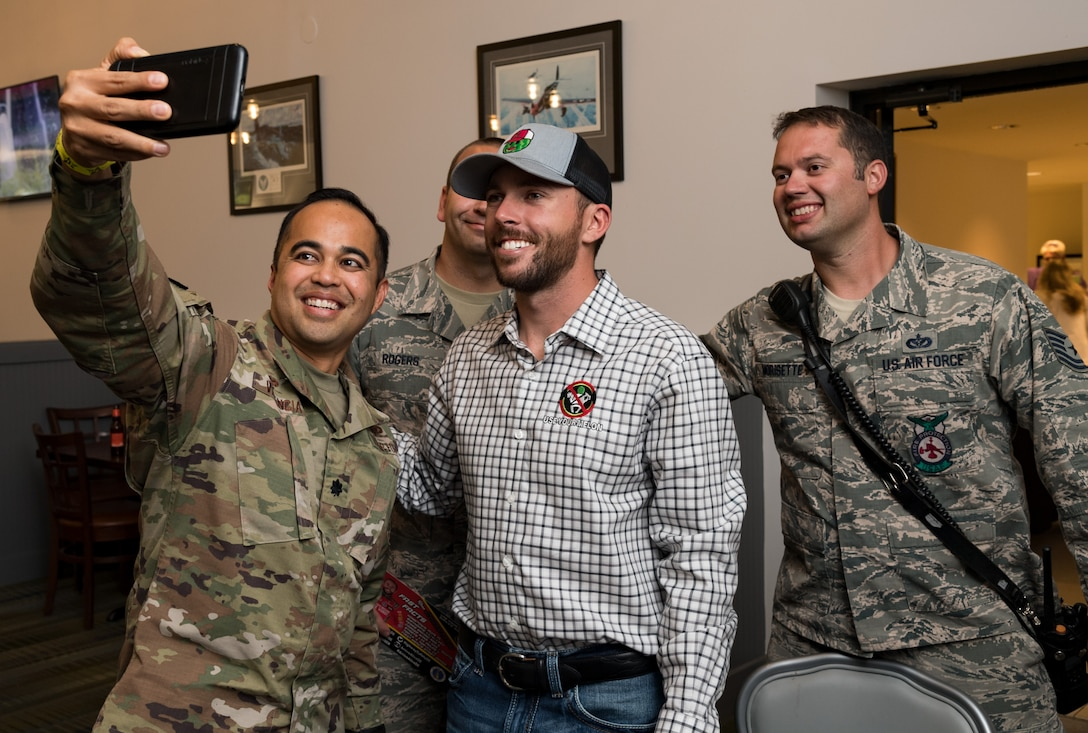 """Lt. Col. Vhance Valencia, 436th Civil Engineer Squadron commander, takes a selfie with Ross Chastain, driver of the No. 15 Low-T Center Chevrolet Camaro, along with Tech. Sgt. Scott Morisette and Staff Sgt. Dustin Rogers, both from the 436th CES fire department Oct. 4, 2019, at Dover Air Force Base, Del. Chastain attended October's First Friday in Hangar 295 at The Landings to sign autographs and meet some of Team Dover's Airmen. He is scheduled to drive in the """"Drydene 400"""" Monster Energy NASCAR Cup Series playoff race on Oct. 6, 2019. (U.S. Air Force photo by Roland Balik)"""