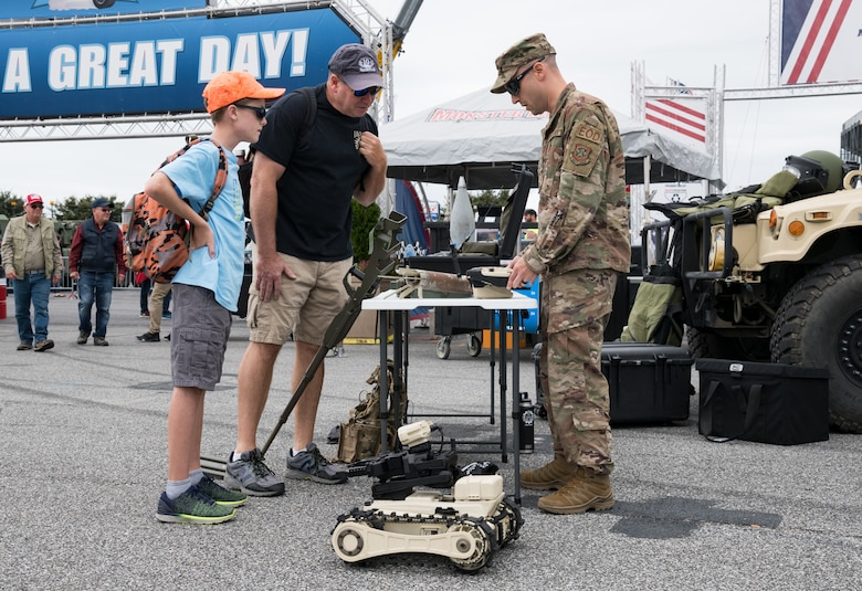 Staff Sgt. Andrew Vitale, 436th Civil Engineer Squadron explosive ordnance disposal craftsman, answers questions from race fans Oct. 6, 2019, at Dover International Speedway, Dover, Del. Members from the 436th CES EOD, Fire Department and 436th Security Forces Squadron set up equipment and vehicle static displays in the Monster Mile Youth Nation area. (U.S. Air Force photo by Roland Balik)