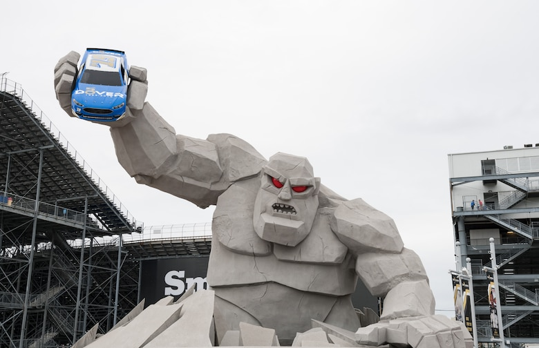 Miles the Monster holds a race car above race fans in Victory Plaza Oct. 6, 2019, at Dover International Speedway, Dover, Del. This race weekend is DIS's 50th Anniversary celebration and the 100th NASCAR Cup Series race in the track's history. (U.S. Air Force photo by Roland Balik)