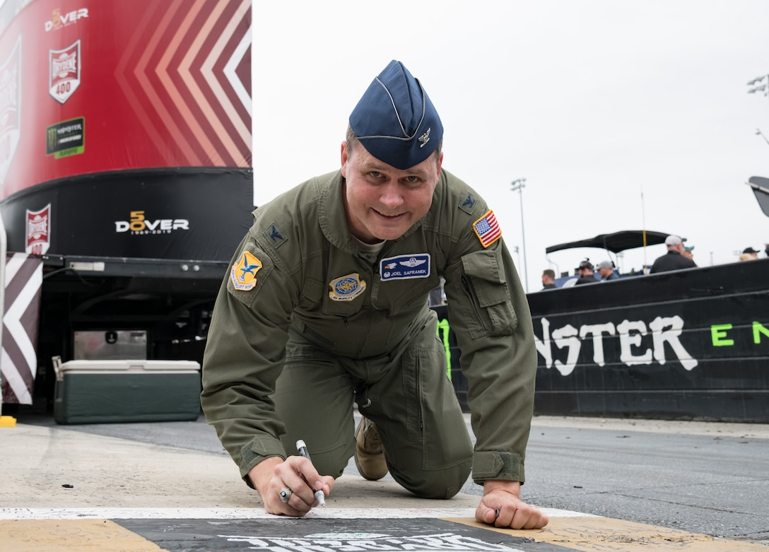 "Col. Joel Safranek, 436th Airlift Wing commander, writes on the racetrack start/finish line Oct. 6, 2019, at Dover International Speedway, Dover, Del. Safranek took the opportunity to write a message on the checkered line prior to the start of the ""Drydene 400"" Monster Energy NASCAR Cup Series playoff race. (U.S. Air Force photo by Roland Balik)"