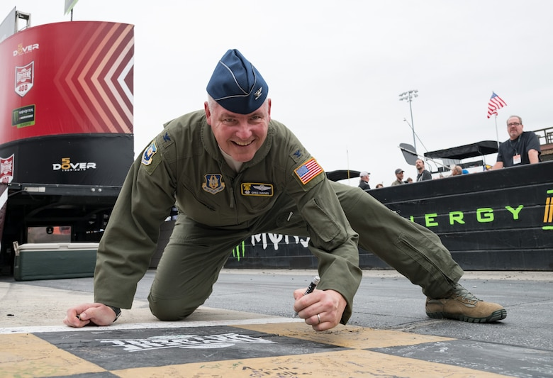 "Col. Gregory Haynes, 512th Airlift Wing commander, writes on the racetrack start/finish line Oct. 6, 2019, at Dover International Speedway, Dover, Del. Haynes took the opportunity to write a message on the checkered line prior to the start of the ""Drydene 400"" Monster Energy NASCAR Cup Series playoff race. (U.S. Air Force photo by Roland Balik)"