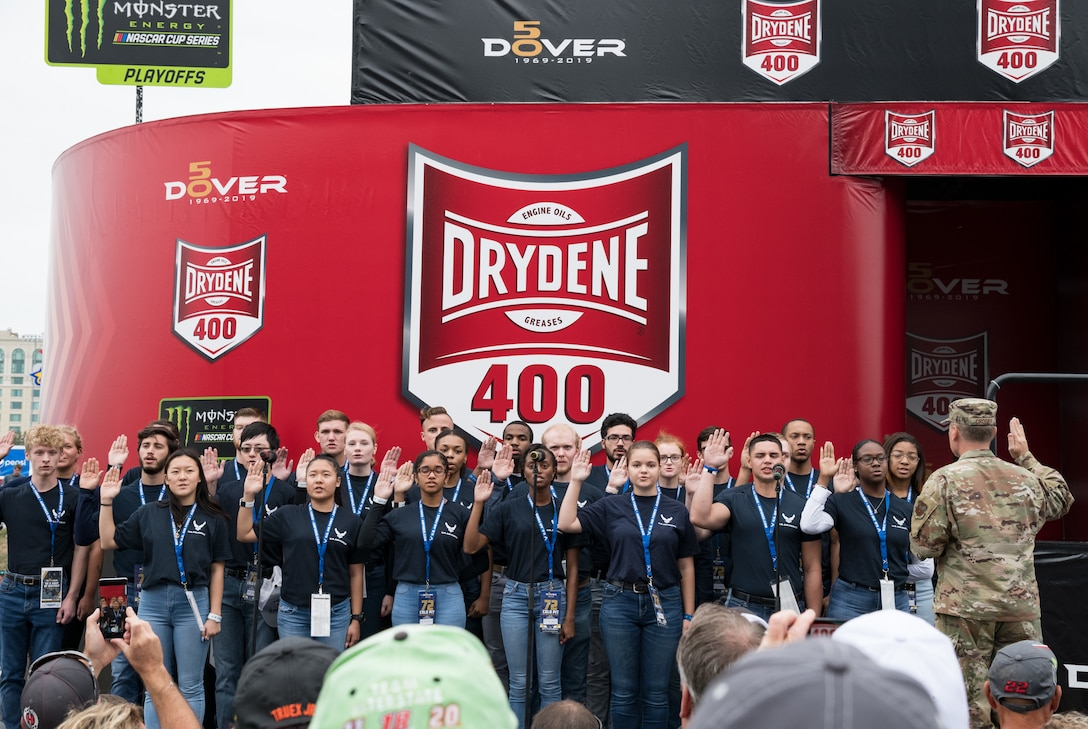 """Maj. Gen. Clinton Crosier, assigned to the Deputy Chief of Staff for Strategy, Integration and Requirements, Headquarters U.S. Air Force, Arlington, Va., administers the oath of enlistment to 26 U.S. Air Force recruits entering the Delayed Entry Program Oct. 6, 2019, at Dover International Speedway, Dover, Del. Crosier administered the oath of enlistment to the recruits prior to the start of the """"Drydene 400"""" Monster Energy NASCAR Cup Series playoff race. (U.S. Air Force photo by Roland Balik)"""