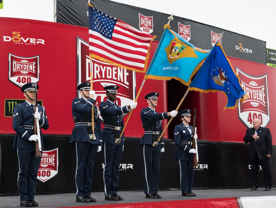 """The Dover Air Force Base Honor Guard presents the colors during the opening ceremony of the """"Drydene 400"""" Monster Energy NASCAR Cup Series playoff race Oct. 6, 2019 at Dover International Speedway, Dover, Del. Team Dover members participated in DIS's 50th Anniversary celebration and the 100th NASCAR Cup Series race in the track's history. (U.S. Air Force photo by Roland Balik)"""