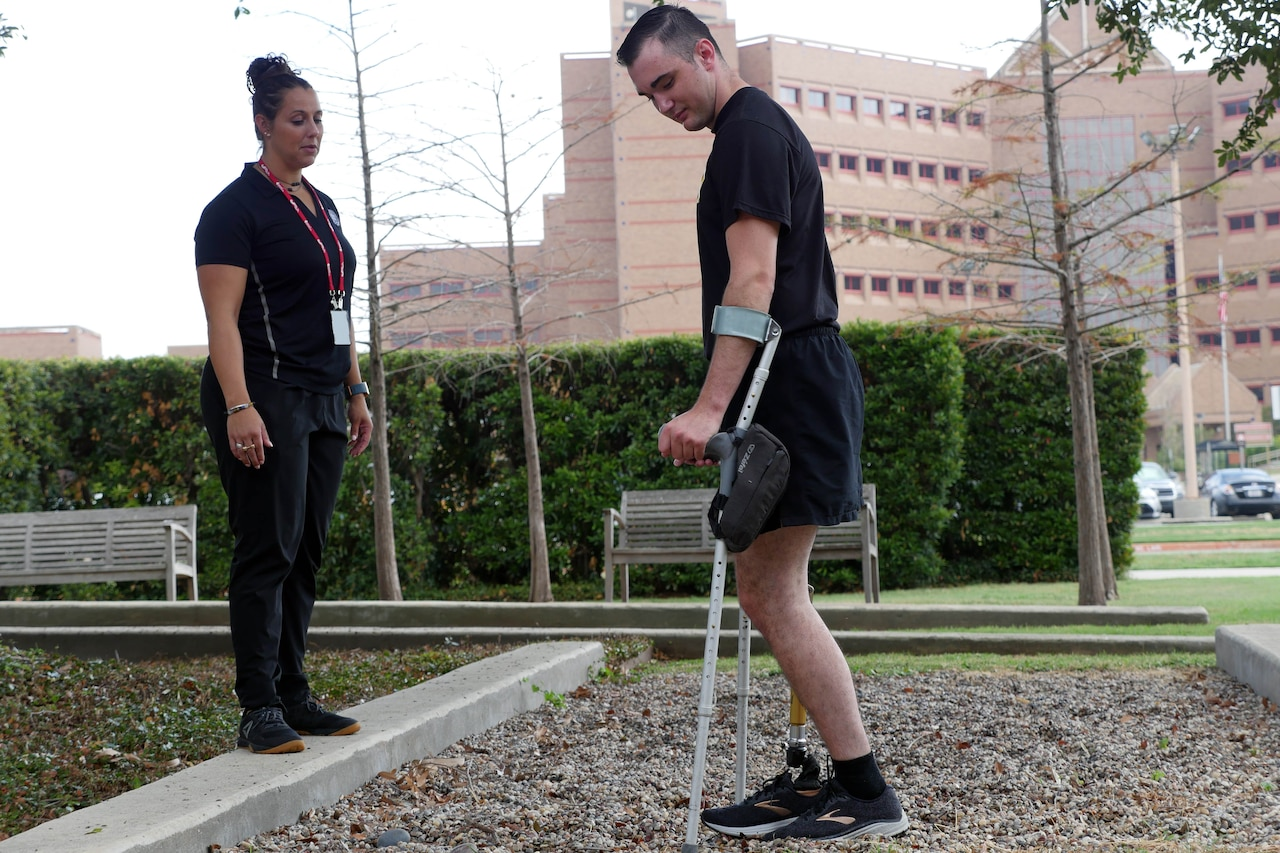 Physical therapist observes as man with prosthetic leg works on learning to walk.