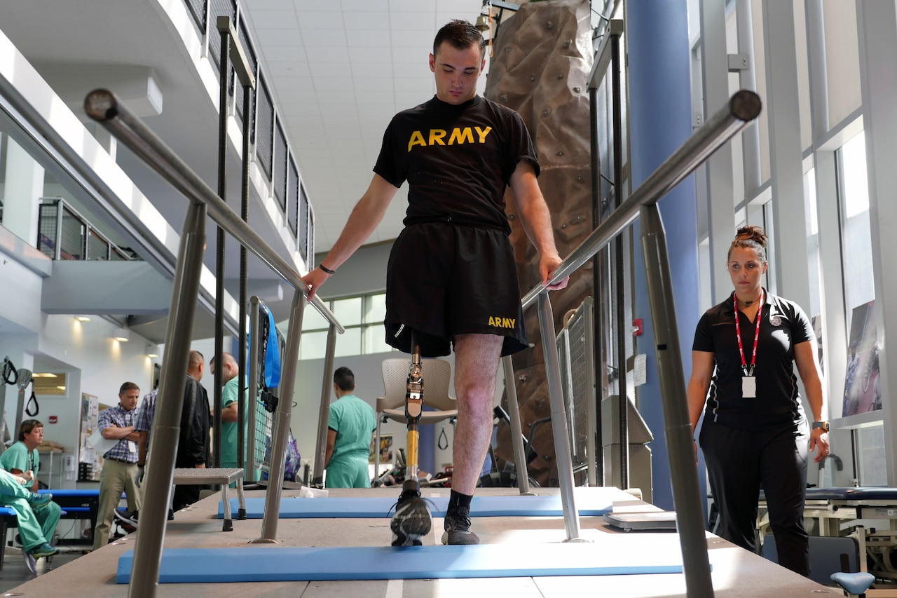 "Man with a prosthetic leg who is wearing black shorts and a T-shirt reading ""ARMY"" walks along rails as physical therapist watches."