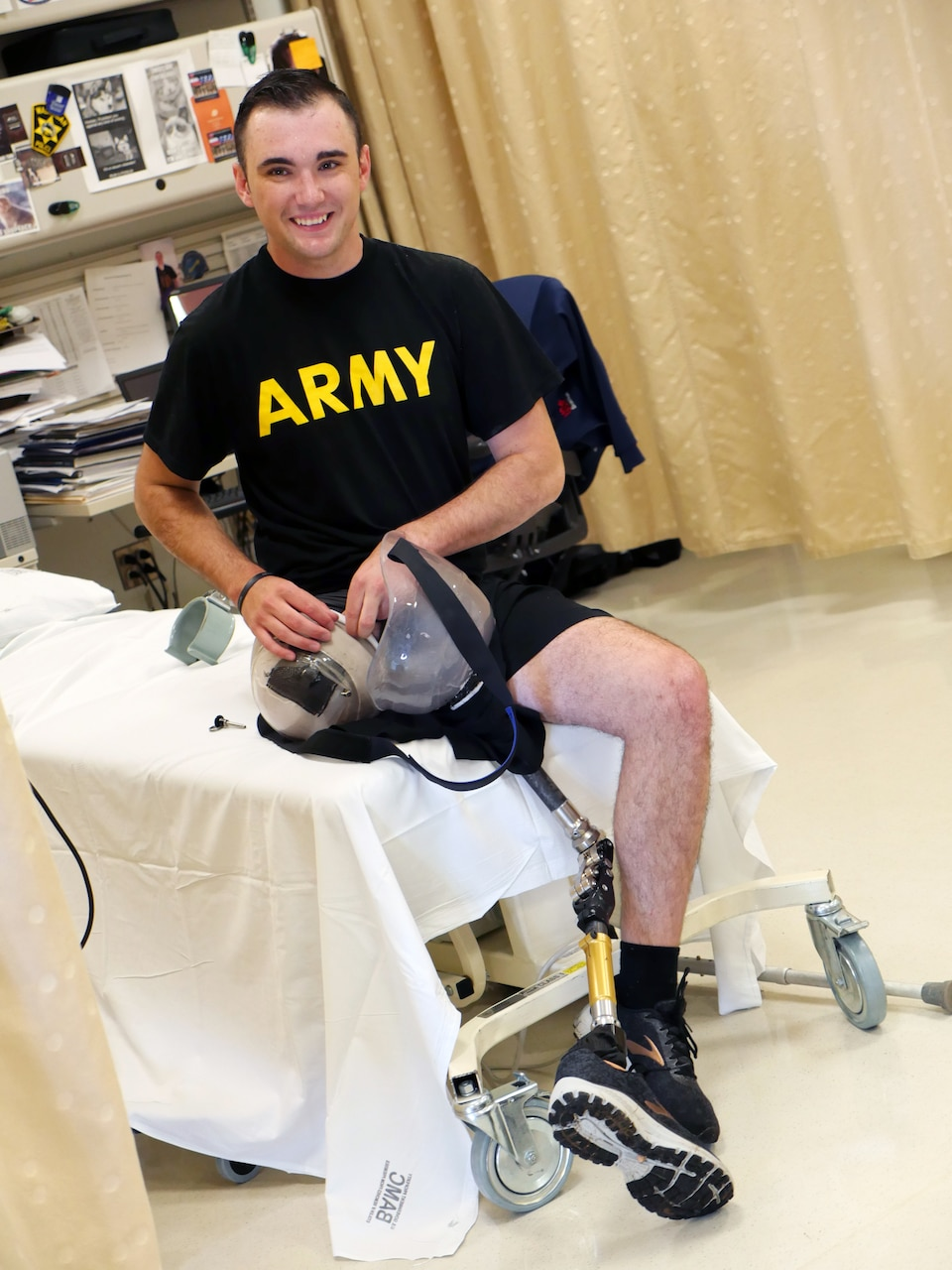"""Man with a prosthetic leg wearing black shorts and a T-shirt reading """"ARMY"""" sits on a rehabilitation facility bed."""