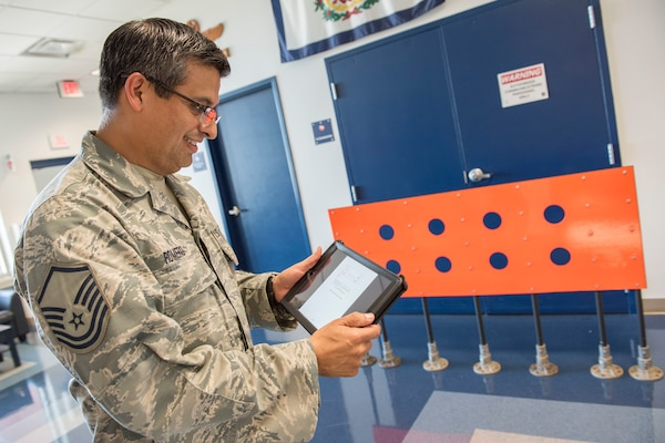 Master Sgt. Alan Romero, 167th Airlift Wing airfield manager, looks at a schematic showing where visual landing zone marker panels would be placed on an airfield for assault landing practice. The orange VLZMP in the photo was designed and fabricated at the 167th AW. Romero, and the airfield management team, are working with officials at the John Murtha Johnstown-Cambria Airport in Johnstown, Pa., to use a runway there for C-17 Globemaster III aircraft assault landing practice. The VLZMP are just one step in a lengthy approval process. (U.S. Air National Guard photo by Senior Master Sgt. Emily Beightol-Deyerle)