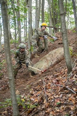 Two Soldiers of the West Virginia Army National Guard's 249th Army Band clear  debris from a fireline during basic wildland fire suppression training, conducted by the West Virginia Division of Forestry in Morgantown, West Virginia, Oct. 3, 2019. The training covered basic wildland fire fighting techniques including understanding fire behavior, suppression tactics and techniques, crew organization, communications, and crew safety and awareness, with the goal of providing WNVG Soldiers the basic skills and experience to operate on a fire line side-by-side with experienced Division of Forestry personnel. (U.S. Army National Guard photo by Edwin L. Wriston)