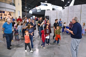 A group of people attend a guided tour of an airplane hangar.