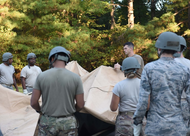 Multiple Airmen spread a plastic cover over a tent.
