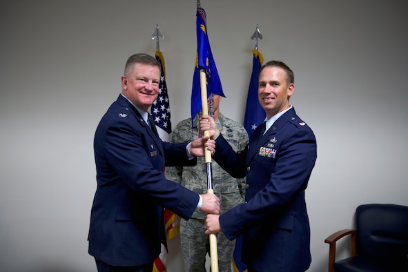 Col. Kent Hanson, 419th Mission Support Group commander, passes the squadron flag to Maj. Brian Weese, the new commander of the 419th Force Support Squadron, during a change of command ceremony