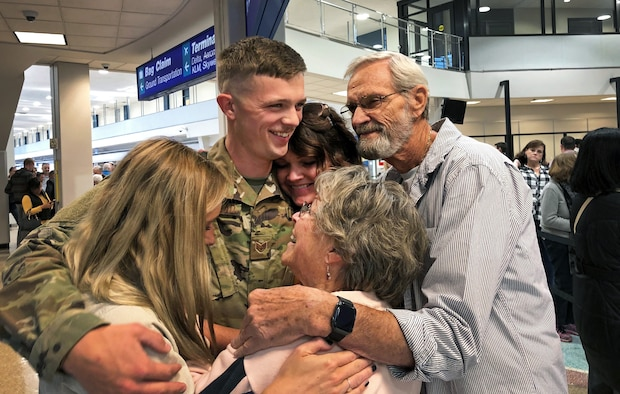 Staff Sgt. Braxton Beckstead, a reservist in the 67th Aerial Port Squadron, hugs his family goodbye before departing on a deployment to the Middle East last week