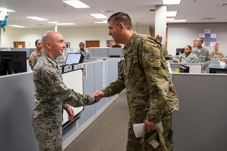 Col. Daniel Walls, right, 23d Wing commander, coins Staff Sgt. Thomas Morris, 23d Comptroller Squadron NCO in charge of financial analysis, Oct. 7, 2019, at Moody Air Force Base, Ga. Morris was recognized for   overseeing the accounting operations more than $150 million and certifying $10 million during the fourth quarter of 2019. Walls visited different components of Moody's Wing Staff Agency to acknowledge their contributions to the mission. (U.S. Air Force photo by Airman Azaria E. Foster)