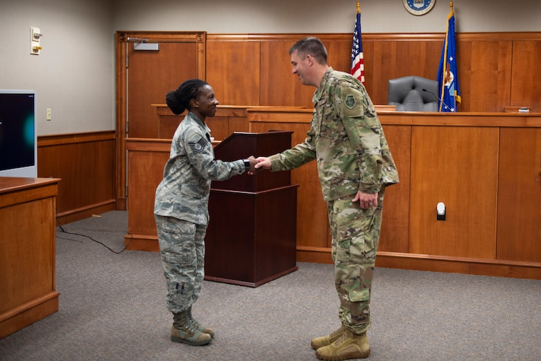 Col. Daniel Walls, right, 23d Wing commander, coins Tech Sgt. Tenesia Parks, 23d Wing Judge Advocate NCO in charge of military justice, Oct. 7, 2019, at Moody Air Force Base, Ga. Parks was recognized for overseeing the management of 35 criminal investigations and helping promote mental readiness by facilitating seven Resiliency Tactical Pause discussions amongst 180 Airmen. Walls visited different components of Moody's Wing Staff Agency to acknowledge their contributions to the mission. (U.S. Air Force photo by Airman Azaria E. Foster)