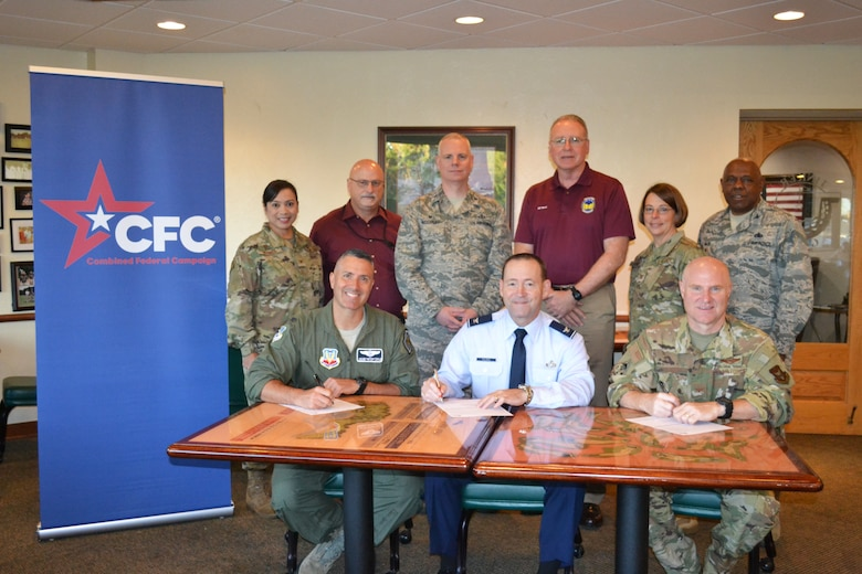 An image of Tinker Senior leaders signing pledge cards for Combined Federal Campaign.