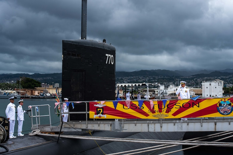JOINT BASE PEARL HARBOR-HICKAM (Sept. 20, 2019) -- Cmdr. Chad Hardt, from Aiken, South Carolina, salutes the ensign during a change of command ceremony for the Los Angeles-class fast-attack submarine USS Tucson (SSN 770) on the submarine piers, Sept. 20. Cmdr. Douglas Pratt, from Nashua, New Hampshire, relieved Hardt as Tucson's commanding officer. (U.S. Navy photo by Mass Communication Specialist 1st Class Michael B. Zingaro/Released)