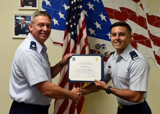 U.S. Air Force Lt. Col. Herbert Millet, 313th Training Squadron commander, presents the 315th Training Squadron Officer Student of the Month award to 2nd Lt. William Chirinos, 315th TRS student, at Brandenburg Hall on Goodfellow Air Force Base, Texas, Oct. 4, 2019. The 315th TRS's vision is to develop combat-ready intelligence, surveillance and reconnaissance professionals and promote an innovative squadron culture and identity unmatched across the U.S. Air Force. (U.S. Air Force photo by Airman 1st Class Zachary Chapman/Released)