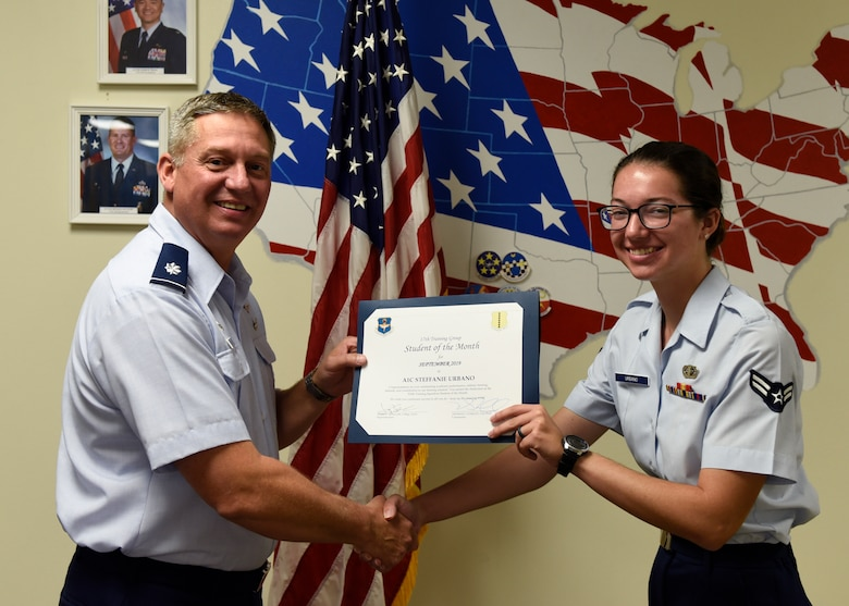 U.S. Air Force Lt. Col. Herbert Millet, 313th Training Squadron commander, presents the 316th Training Squadron Student of the Month award to Airman 1st Class Steffanie Urbano, 316th TRS student, at Brandenburg Hall on Goodfellow Air Force Base, Texas, Oct. 4, 2019. The 316th TRS's mission is to conduct U.S. Air Force, U.S. Army, U.S. Marine Corps, U.S. Navy and U.S. Coast Guard cryptologic, human intelligence and military training. (U.S. Air Force photo by Airman 1st Class Zachary Chapman/Released)
