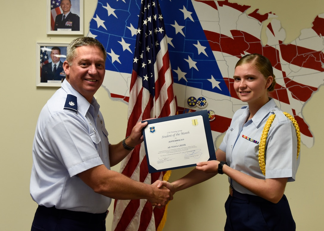 U.S. Air Force Lt. Col. Herbert Millet, 313th Training Squadron commander, presents the 315th Training Squadron Student of the Month award to Airman Tessa Greer, 315th TRS student, at Brandenburg Hall on Goodfellow Air Force Base, Texas, Oct. 4, 2019. The 315th TRS's vision is to develop combat-ready intelligence, surveillance and reconnaissance professionals and promote an innovative squadron culture and identity unmatched across the U.S. Air Force. (U.S. Air Force photo by Airman 1st Class Zachary Chapman/Released)