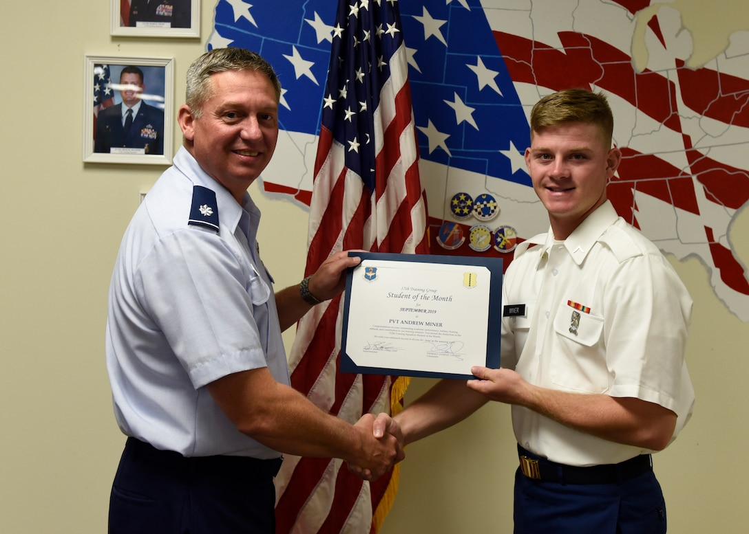 U.S. Air Force Lt. Col. Herbert Millet, 313th Training Squadron commander, presents the 312th Training Squadron Student of the Month award to U.S. Army Pvt. Andrew Miner, 312th TRS student, at Brandenburg Hall on Goodfellow Air Force Base, Texas, Oct. 4, 2019. The 312th TRS's mission is to provide Department of Defense and international customers with mission-ready fire protection and special instruments graduates and provide mission support for the Air Force Technical Applications Center. (U.S.  Air Force photo by Airman 1st Class Zachary Chapman/Released)