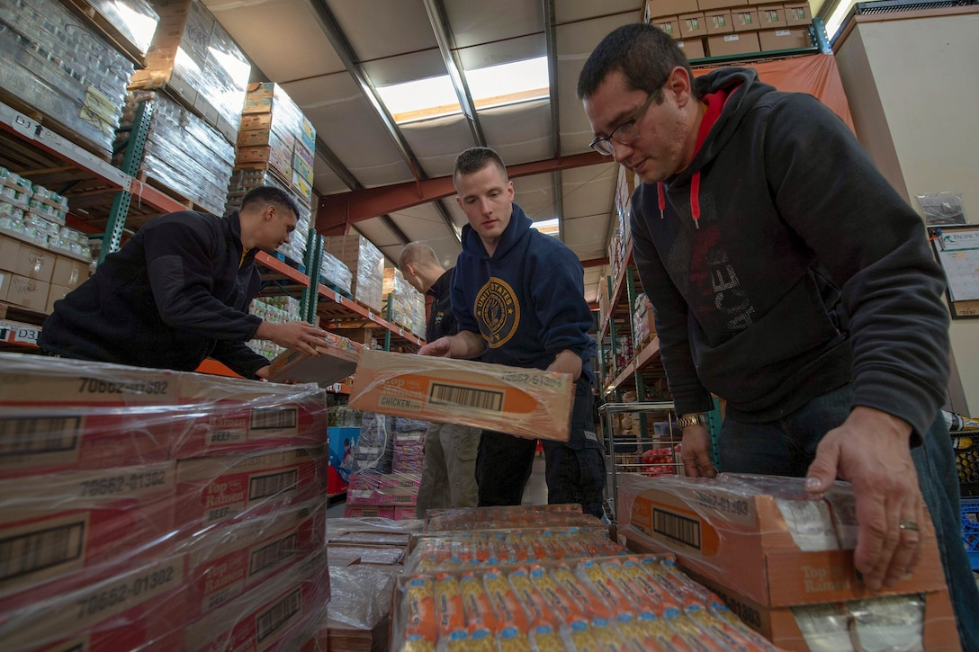 Sailors handle pallets of packaged food.