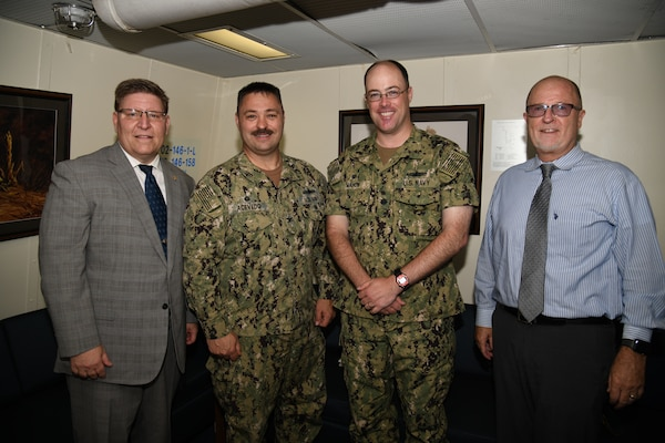 NSWC PHD Commanding Officer Capt. Ray Acevedo, Technical Director Paul Mann, and Deputy Technical Director Vance Brahosky pose for a photo with USS Ralph Johnson (DDG 114) Commanding Officer Cmdr. Casey Mahon during a meet and greet aboard the ship, Aug. 26.