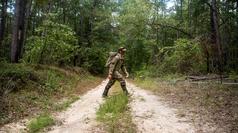 A Survival, Evasion, Resistance and Escape Specialist assigned to the 437th Operations Support Squadron walks across a dirt road during a survival, evasion, resistance, and escape exercise August 21, 2019 in North, South Carolina. SERE specialists assigned to the 437th Operations Support Squadron conducted this exercise in order to identify potential areas of improvement in both SERE training and equipment provided to aircrew in case of a potential isolating event. (U.S. Air Force photo/Airman 1st Class Duncan C. Bevan)